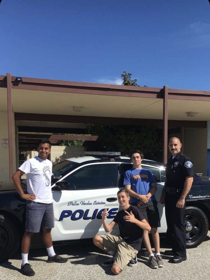 Members of the Student Chief Council (SCC), Pallav Chaturvedi, Lane Karlitz, and Johnny McKay, pose in front of Chief Velez's car.